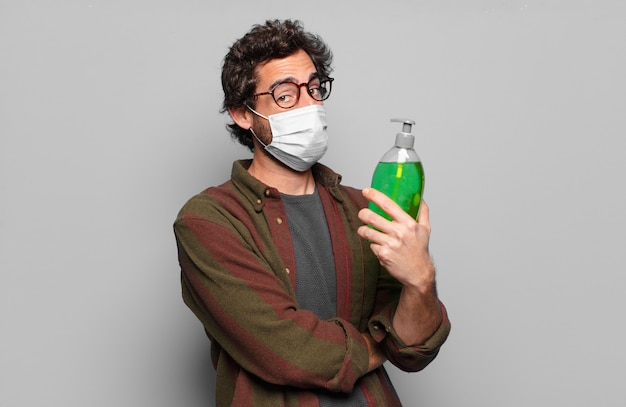 医療マスクを持つ若いひげを生やした男