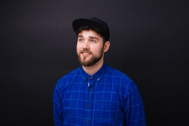 Young bearded man with blue eyes and blue shirt looking in the future dreaming about something.