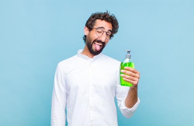 Молодой бородатый мужчина с веселым, беззаботным, бунтарским отношением, шутит и высунул язык, веселится