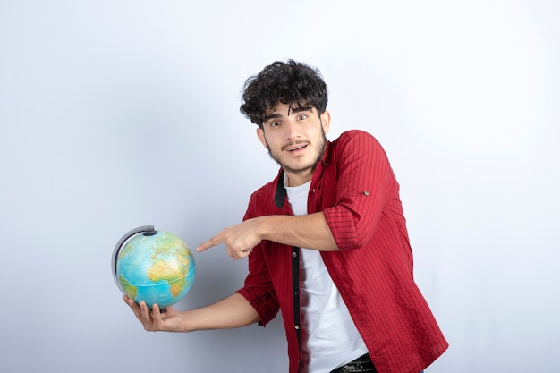 Young bearded man with curly hair choosing for new travel experience.