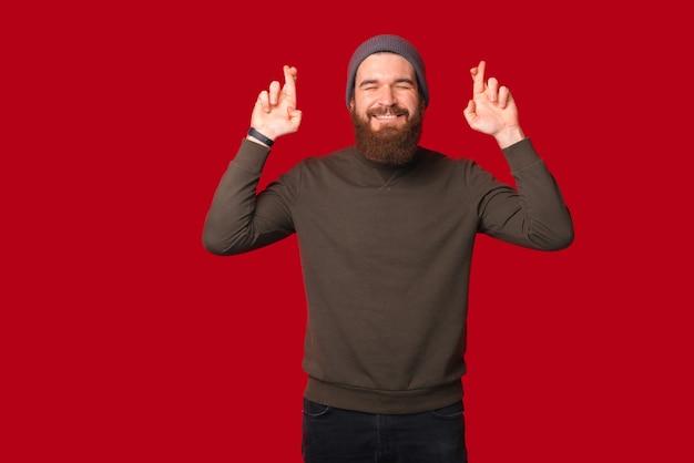 目を閉じたあごひげを生やした若い男が立って、希望を求めて指を交差させています。