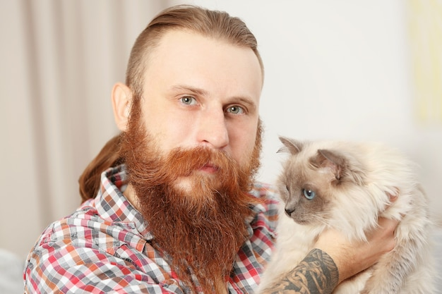 Young bearded man with fluffy cat at home