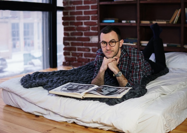 Young bearded man with glasses on bed