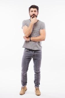 Молодой бородатый мужчина, скрестив руки на серой стене