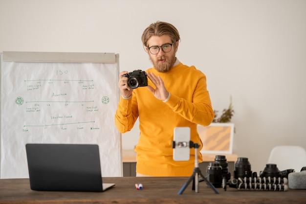 스마트 폰 카메라 앞에서 온라인 청중에게 스톡 사진을 찍는 방법을 설명하는 photocamera와 젊은 수염 난된 남자