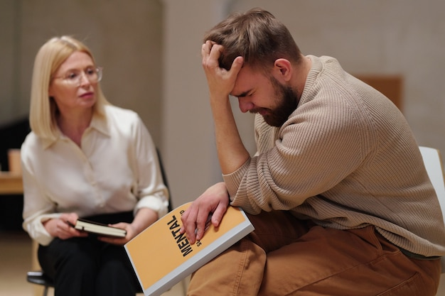 Young bearded man with psychological problem or trauma holding his head in hand while sitting by mature blond female counsellor