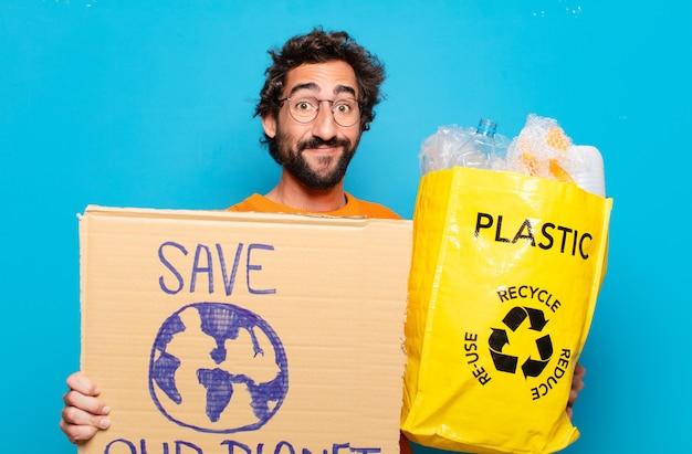 リサイクルボードとプラスチックの若いひげを生やした男