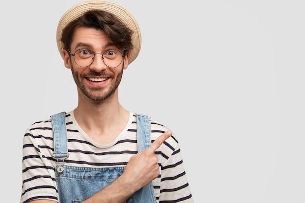 丸いメガネとデニムのオーバーオールを持つ若者を生やした