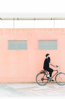 Young bearded man with shoulder bag riding a bike on the city street