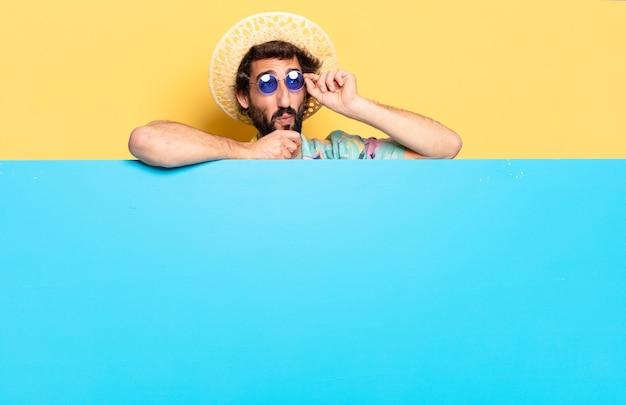 サングラスと青いボードを持つ若いひげを生やした男