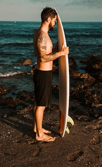 Young bearded man with surf board on shore near water