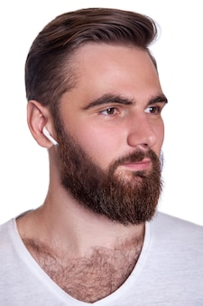 Young bearded man with wireless earphones on his ears. studio shot, isolated on white background.