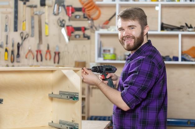 家具工場で働く若いひげを生やした男。