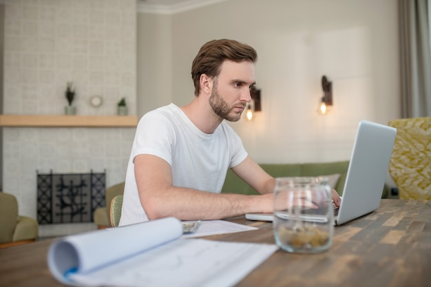 Young bearded man working on a laptop and looking concentrated