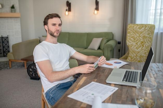 Молодой бородатый мужчина работает на ноутбуке и выглядит сосредоточенным