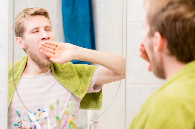 Young bearded man yawn in front of mirror in the bathroom