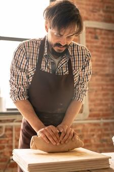 Молодой бородатый мастер гончарного дела замешивает глину, готовит ее к дальнейшей обработке и делает столовые приборы.