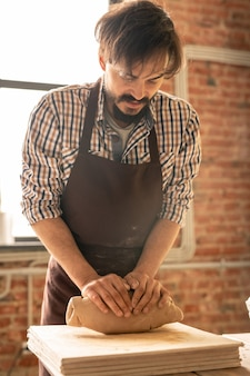 Young bearded master of pottery kneading clay while preparing it for further processing and making eathenware