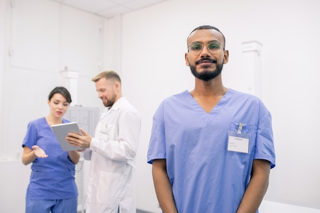 タッチパッドを使用して2人の同僚の背景にカメラの前に立っている若いひげを生やした混血インターン