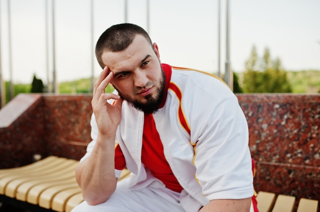 Молодой бородатый мускулистый мужчина носить белый спортивный костюм с красной рубашке