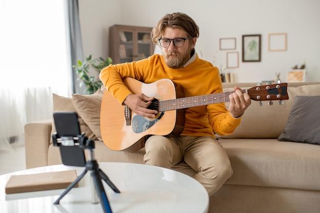 リビングルームのソファに座って、スマートフォンのカメラの前でギターを弾くカジュアルウェアの若いひげを生やしたミュージシャンまたは音楽教師