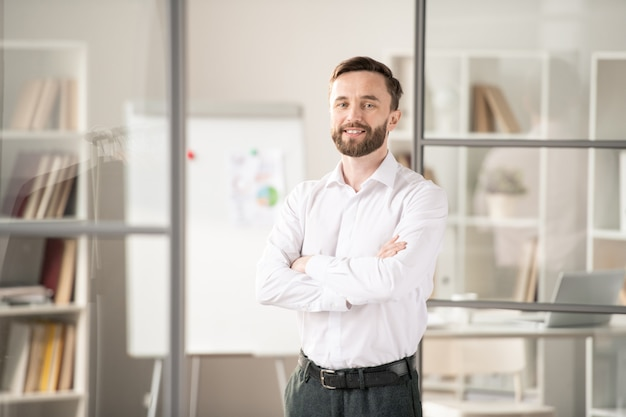 Young bearded office worker crossing his arms on chest while posing in workplace