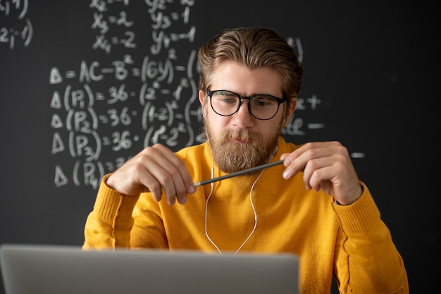 Young bearded pensive teacher in eyeglasses listening to one of students while looking at laptop display during online lesson of algebra