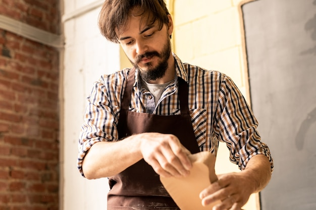 Young bearded potter in apron holding clay workpiece while going to process it in pottery wheel during work