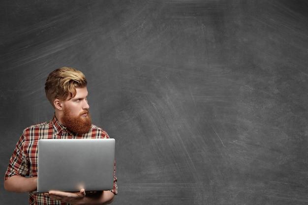 Молодой бородатый школьный учитель со стильной стрижкой, одетый в красную клетчатую рубашку, использует портативный компьютер, работая в классе после уроков, проверяя документы, глядя в сторону с серьезным выражением лица