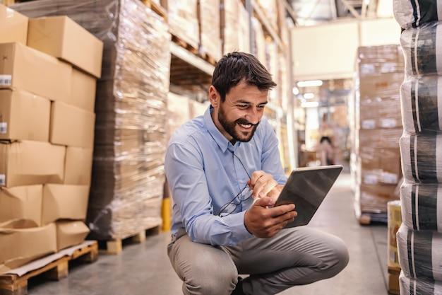 Молодой бородатый улыбающийся руководитель сидит на корточках на складе и использует планшет для проверки товаров