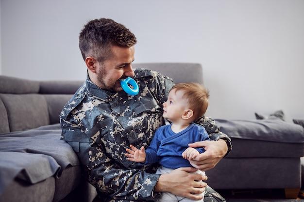 若いひげを生やした兵士が制服を着て床に座って、最愛の息子を膝の上に抱えています。口の中にシリコンおしゃぶりを持っている人。