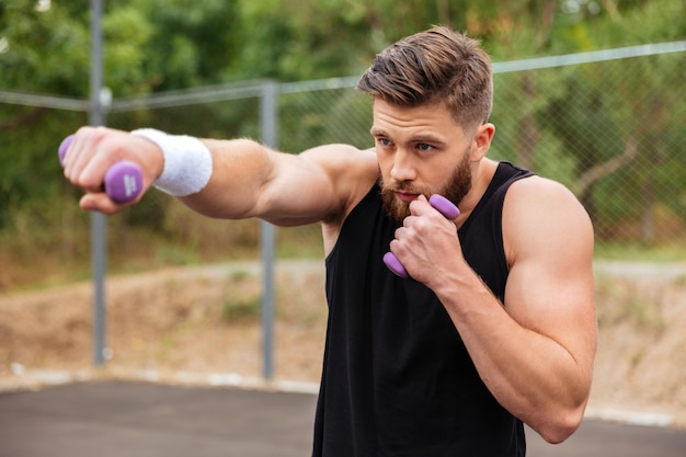 Молодой бородатый спортсмен делает тренировку с маленькими гантелями на открытом воздухе