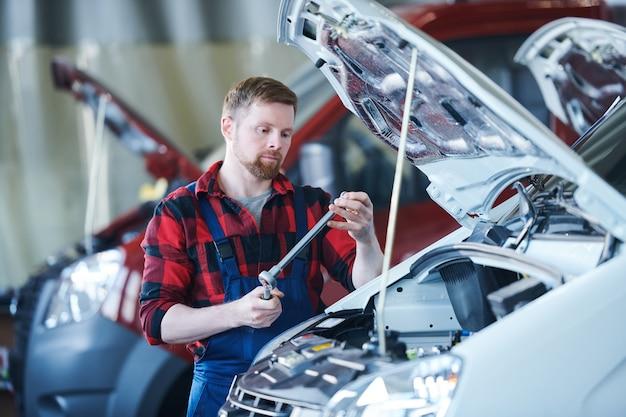 小さな金属の詳細を修正するためのハンドツールを選択する車の修理サービスの若いひげを生やしたスタッフ