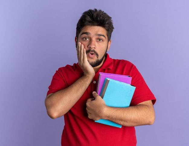 本を持っている赤いポロシャツを着た若いひげを生やした学生の男が驚いて、青い壁の上に立って驚いた
