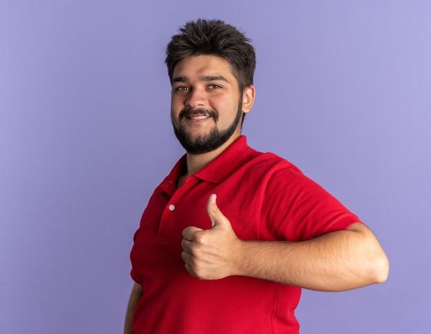 赤いポロシャツを着た若いひげを生やした学生の男が幸せそうに見え、肯定的な笑顔が立っている親指を現して