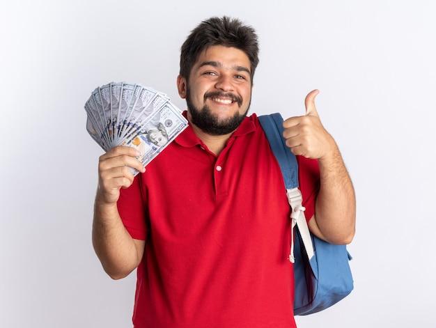 赤いポロシャツを着た若いひげを生やした学生の男が、航空券とグローブを保持しているバックパックを持ち、白い壁の上に立って笑顔で親指を立てている