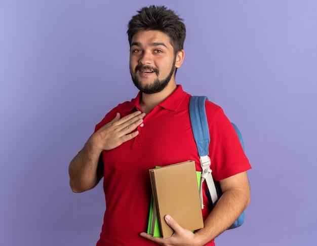 赤いポロシャツを着た若いひげを生やした学生の男がバックパックを持ち、胸に手をつないで本を持ち、青い壁の上に陽気に立って感謝の気持ちを持って笑顔を浮かべている