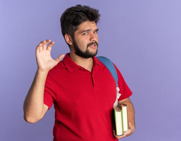 青い背景の上に立っている猫のように爪のジェスチャーを作るカメラを見て本を保持しているバックパックと赤いポロシャツの若いひげを生やした学生の男