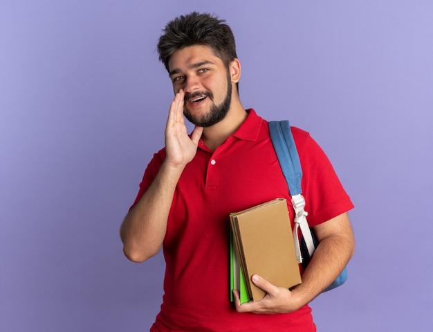 青い背景の上に幸せで前向きに立っている口の近くの手で秘密をささやくカメラを見て本を保持しているバックパックと赤いポロシャツの若いひげを生やした学生の男
