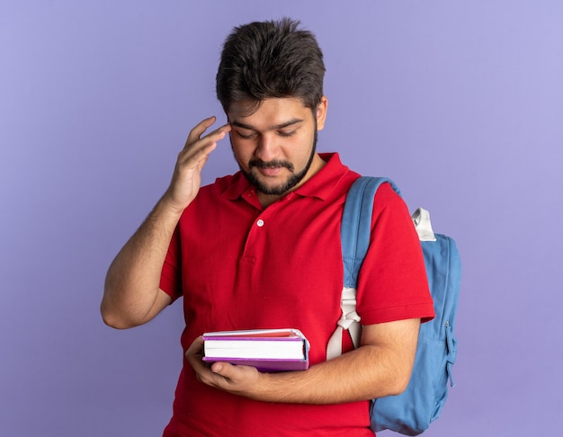 赤いポロシャツを着た若いひげを生やした学生の男が本を持ってバックパックを見て、自信を持って幸せで、青い壁の上に前向きに立っている
