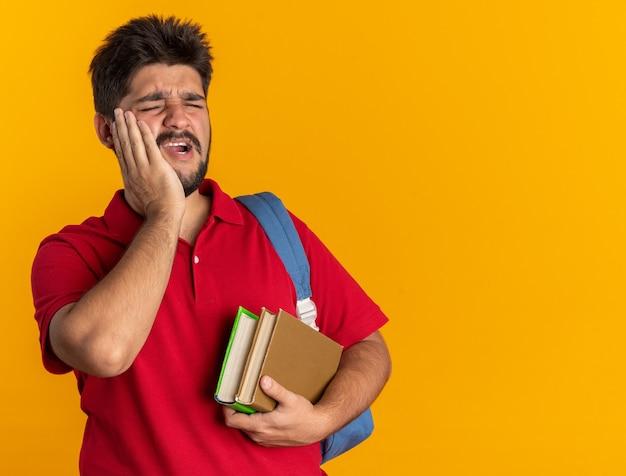 オレンジ色の背景の上に立っている歯痛を感じて彼の頬に触れて気分が悪いように見える本を保持しているバックパックと赤いポロシャツの若いひげを生やした学生の男