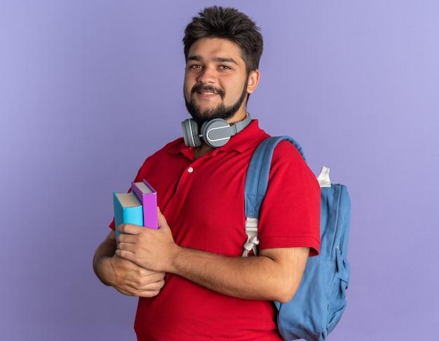 赤いポロシャツを着た若いひげを生やした学生男がバックパックを持ち、首にヘッドフォンを付けて本を持ち、幸せで前向きな笑顔の立っている