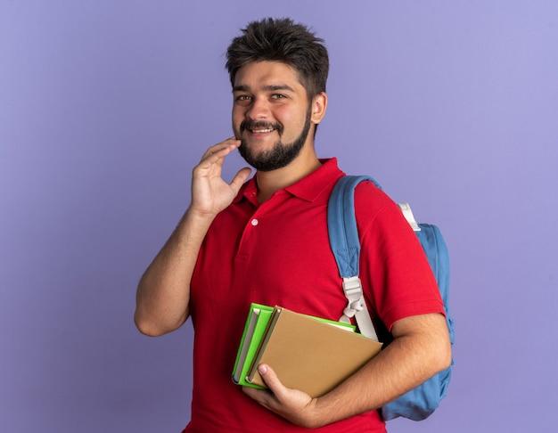 青い壁の上に立っている顔に恥ずかしがり屋の笑顔で本を保持しているバックパックと赤いポロシャツの若いひげを生やした学生男
