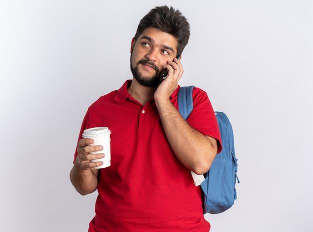 白い背景の上に立っている携帯電話で話している間自信を持って笑っているコーヒーカップを保持しているバックパックと赤いポロシャツの若いひげを生やした学生の男