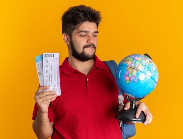 Молодой бородатый студент-парень в красной рубашке поло с рюкзаком, держащим глобус и авиабилеты, выглядит заинтригованным и счастливым, стоя на оранжевом фоне