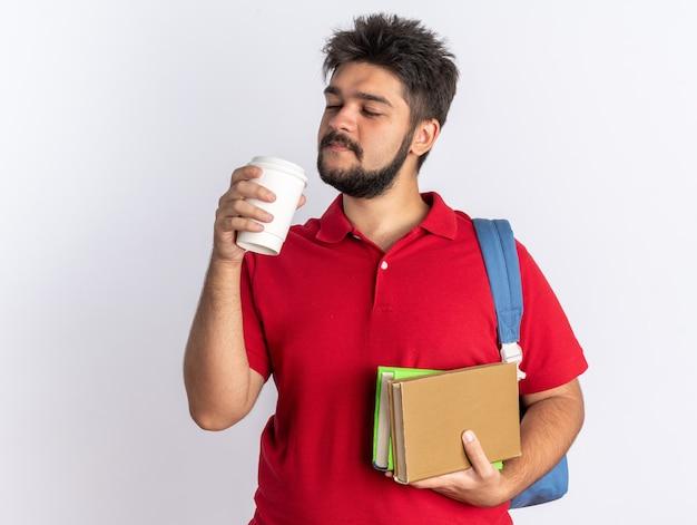 Молодой бородатый студент-парень в красной рубашке поло с рюкзаком, держащим тетради и кофейную чашку, уверенно улыбаясь, стоя на белом фоне