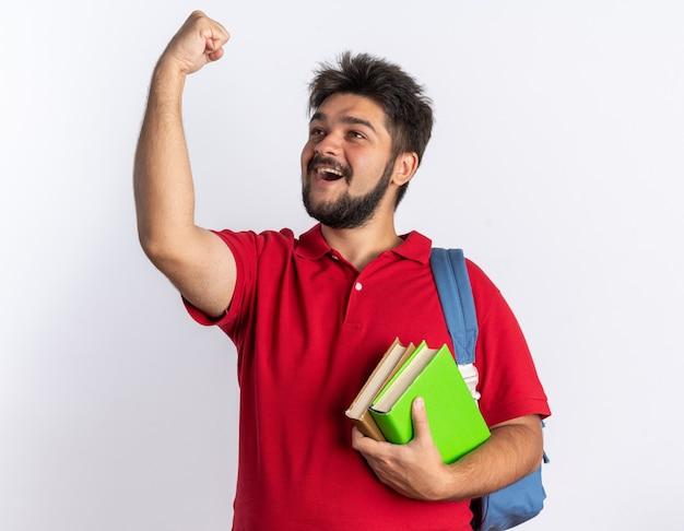 赤いポロシャツを着た若いひげを生やした学生の男が、ノートを持ったバックパックを持ち、拳を握りしめ、白い壁の上に立って成功を喜んで喜んでいる