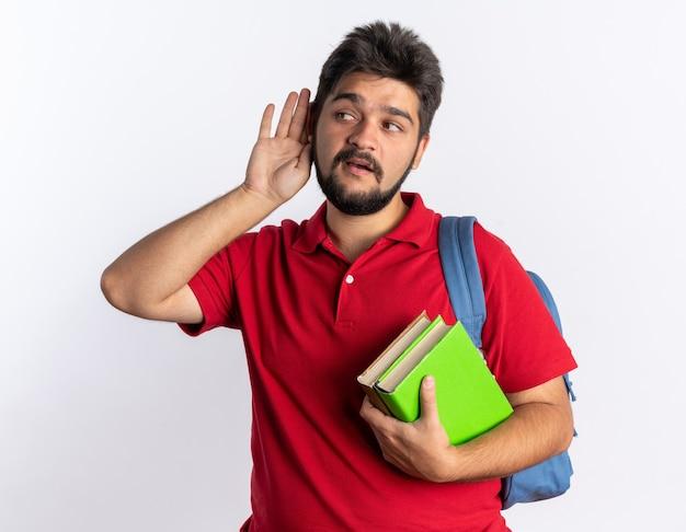 赤いポロシャツを着た若いひげを生やした学生の男が、興味をそそられた立っているのを聴こうとして、ノートを持ち、耳に手を当てた