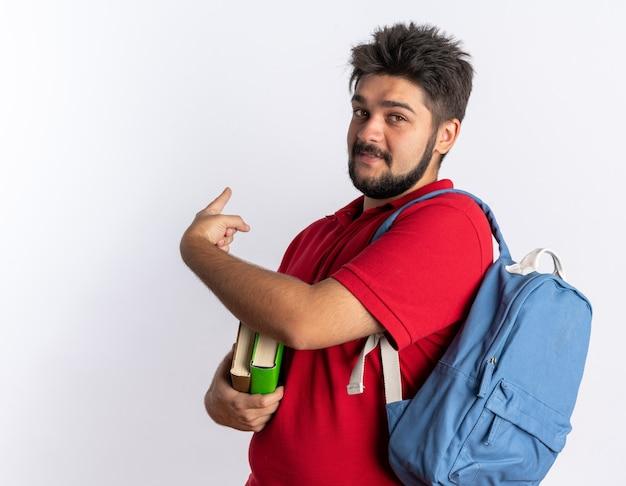 Молодой бородатый студент-парень в красной рубашке поло с рюкзаком держит ноутбуки, выглядит счастливым и позитивным, указывая указательным пальцем назад