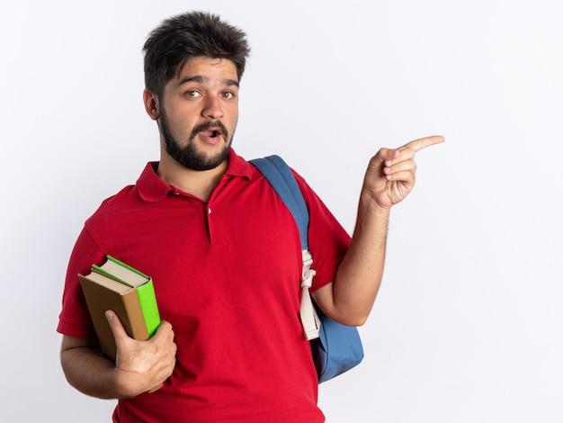 Молодой бородатый студент-парень в красной рубашке поло с рюкзаком, держащий ноутбуки, выглядит счастливым и удивленным, указывая указательным пальцем в сторону, стоя